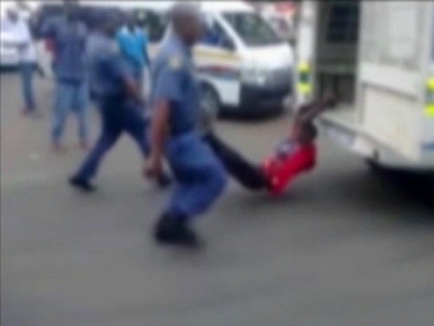 South African police caught on camera dragging handcuffed man behind van